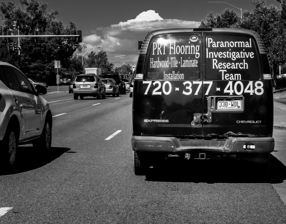 Van in traffic with ads for flooring and paranormal investigation