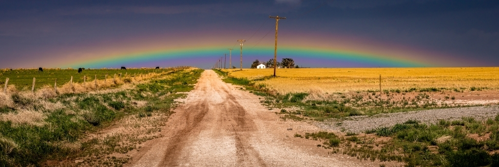 Rainbow low in sky with country road in foreground