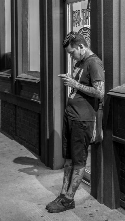 Man relaxing outside of tatoo parlor