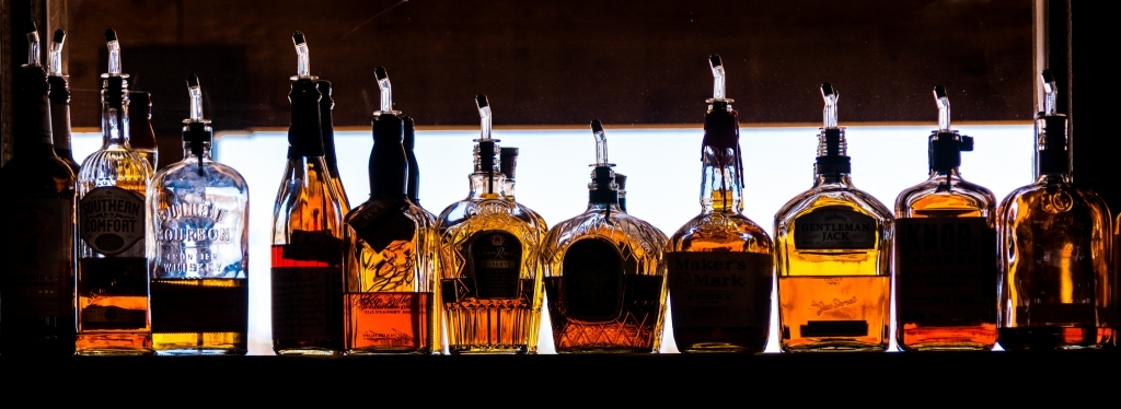 Backlit row of whiskey bottles