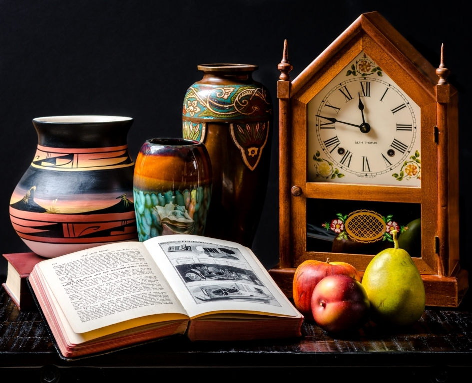 Still life of book, fruit, vases, and clock